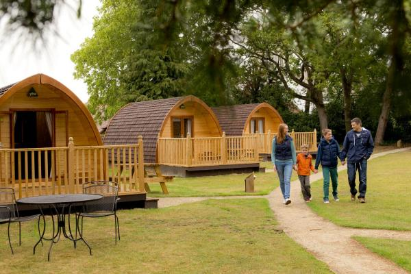 Family walking along the camping pods at YHA