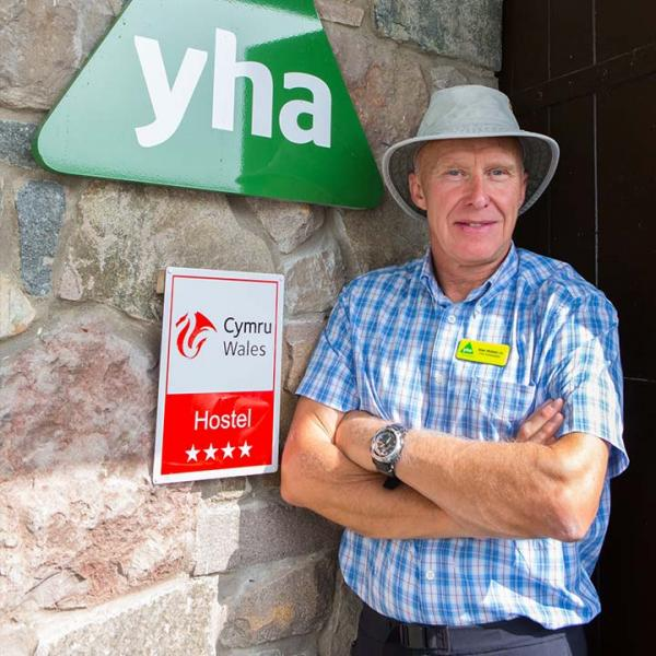 YHA Ambassador Alan Hinkes standing outside a youth hostel
