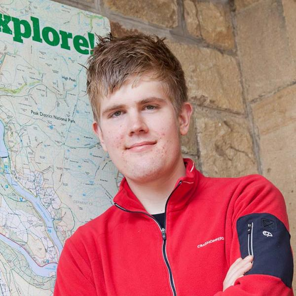 YHA Ambassador Alex Staniforth standing outside a youth hostel