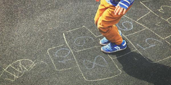 Young male playing hopscotch
