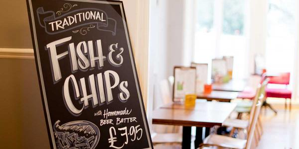 YHA Brighton Food and Drink board promoting fish and chips