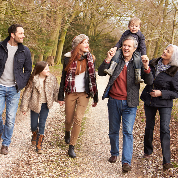 Family of 6 walking through a wooded area in the countryside