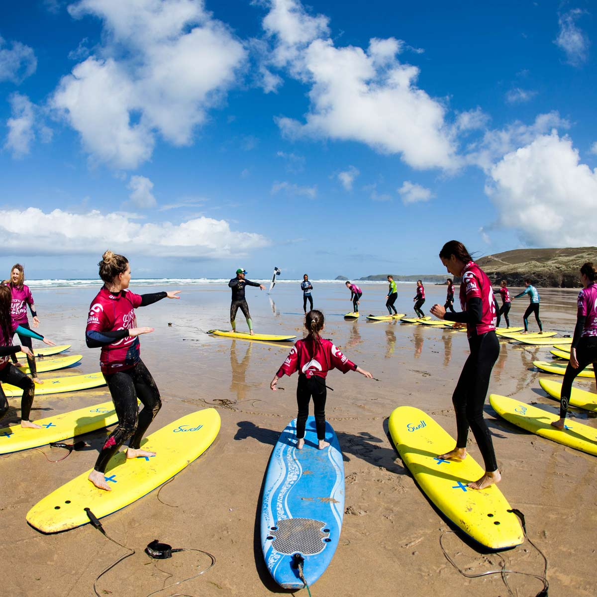 Groups of young people learning to surf on the beach